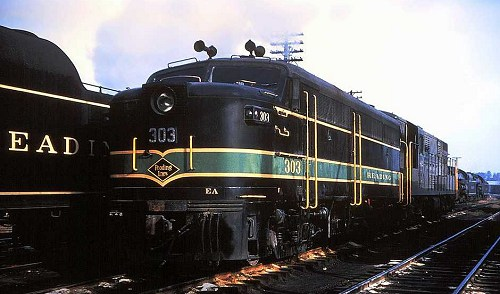 Reading Alco FA-1 #303 shown mated to a Trainmaster, next to a line of stored steam locomotives sometime after 1956.